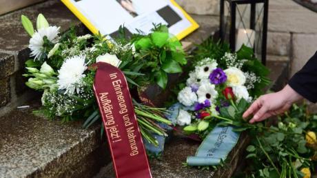 Teilnehmer einer Mahnwache haben zum Gedenken an Oury Jalloh Blumen und Kerzen an einer Treppe vor dem Polizeirevier in Dessau-Roßlau niedergelegt.