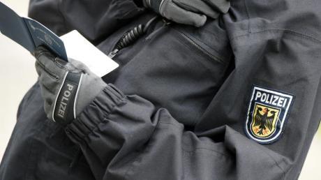 Ein Polizist überprüft Personalien. Beim Racial Profiling werden Menschen auf Grundlage von Stereotypen und äußerlichen Merkmalen als verdächtig eingestuft und überprüft.