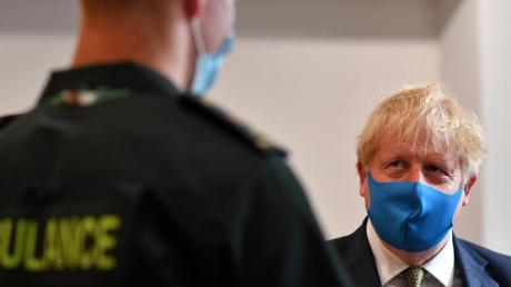 Premier Boris Johnson spricht während eines Besuchs im Hauptquartier des London Ambulance Service NHS Trust mit einem Sanitäter.