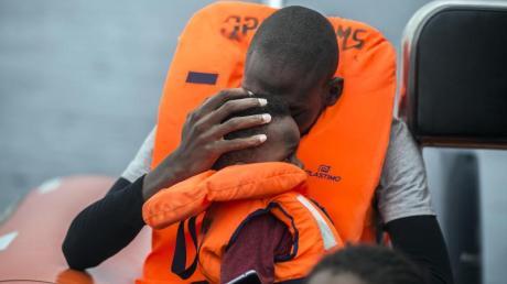 Ein Mann hält seinen Sohn im Arm, nachdem er gemeinsam mit anderen Flüchtlingen gerettet wurde.