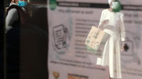 Frauen mit medizinischem Mundschutz spiegeln sich in einem Fenster des Gebäudes der südafrikanischen Sozialversicherungsbehörde (SASSA).
