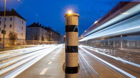 Eine Blitzsäule mit kombinierter Überwachung von Rotlicht und Geschwindigkeit an einer Ampelkreuzung.