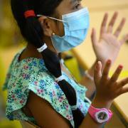 Eine Schülerin trägt im Unterricht eine Schutzmaske.