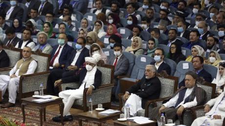 Der afhanische Präsident Aschraf Ghani (M, mit Maske) und Spitzenpolitiker Abdullah Abdullah (r. daneben), der die Versammlung leitet.