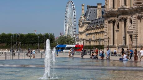 Passanten kühlen sich neben dem Brunnen vor dem Louvre in Paris ab.