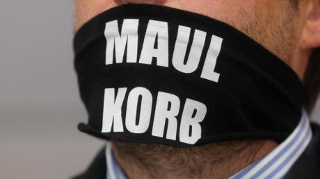 Sven Liebich trägt im Gerichtssaal in Halle einen Mundschutz mit der Aufschrift «Maulkorb».
