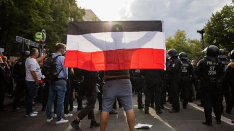 Ein Mann hält eine Reichsflagge bei einem Protest gegen die Corona-Maßnahmen.