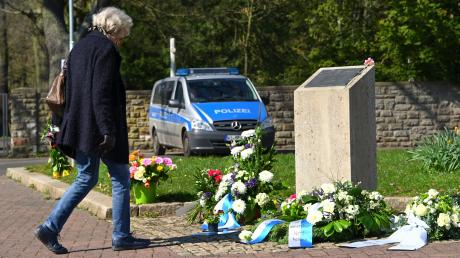 Eine Frau legt am Gedenkstein für die NSU-Opfer auf dem Halitplatz in Kassel Blumen ab.