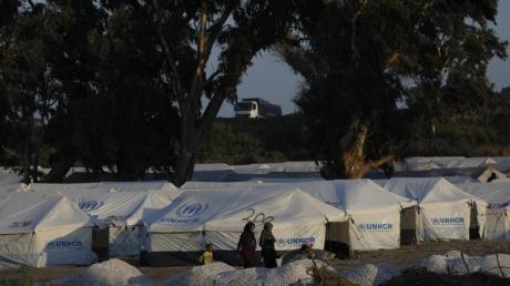 Migranten vor neuen Zelten in einem provisorischen Lager in der Nähe der Inselhauptstadt Mytilini.
