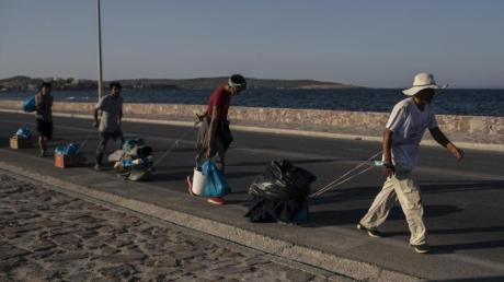Flüchtlinge auf Lesbos ziehen ihre Habseligkeiten hinter sich her.