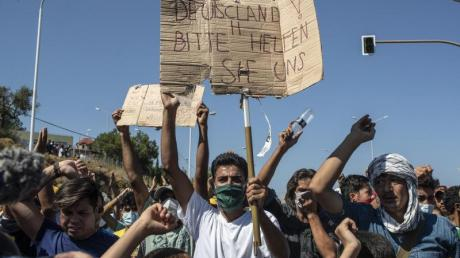 Ein Flüchtling auf Lesbos hält ein Plakat mit der Aufschrift «Deutschland, bitte helfen sie uns». FGriechenland helfen»).