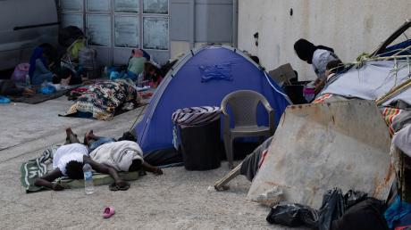 Migranten schlafen neben einem Zelt in der Nähe der Stadt Mytilene an der nordöstlichen Seite der Insel Lesbos. Deutschland will Familien mit Kindern aufnehmen.