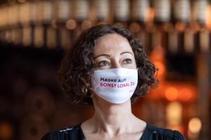 Maske trägt längst nicht jeder. Mit Sprüchen auf Plakaten, Bierdeckeln und Masken sollen Gäste in Berlin an die Corona-Schutzmaßnahmen erinnert werden.