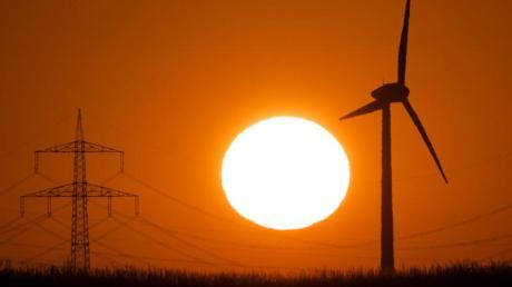 Die Silhouette eines Windrades (r) zeichnet sich vor der aufgehenden Sonne ab.