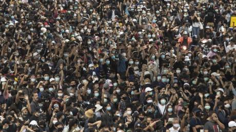 Pro-demokratische Demonstranten zeigen bei einem Protest auf dem Hauptbahnhof den Dreifingergruß als Symbol des Widerstands.