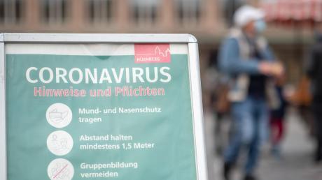 Aufgepasst: Ein Schild informiert Passanten auf dem Hauptmarkt in Nürnberg über die Maskenpflicht und weitere Corona-Verhaltensregeln.