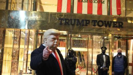 Ein Mann mit einer Trump-Maske in der Hand gestikuliert vor dem Trump Tower, der von einem Polizisten einer Spezialeinheit des NYPD auf der 5th Avenue in Manhattan am Vorabend der Präsidentschaftswahlen gesichert wird.