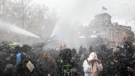 Die Polizei setzt bei einer Demonstration gegen die Corona-Einschränkungen der Bundesregierung am Brandenburger Tor unweit des Reichstagsgebäudes (hinten) Wasserwerfer ein.