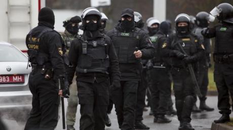Bereitschaftspolizisten stehen am Rande eines Protests von Oppositionellen.