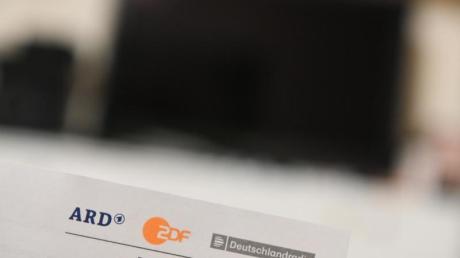 Ein Anschreiben des Beitragsservice für die Rundfunkgebühren ist vor einem Fernseher zu sehen. In Sachsen-Anhalt stemmen sich CDU und AfD gegen die Erhöhung des Rundfunkbeitrags in Deutschland.
