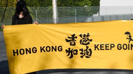 Zwei junge Frauen halten ein Transparent mit der Aufschrift «Hong Kong keep going» bei einer Menschenrechtsaktion vor dem Bundeskanzleramt. Menschenrechtsverletzungen in Ländern wie China, können von der Europäischen Union künftig deutlich einfacher sanktioniert werden.