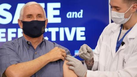 Der amtierende US-Vizepräsident Mike Pence (l) erhält eine Impfung mit dem Corona-Impfstoff von Pfizer-Biontech im Eisenhower Executive Office Building auf dem Gelände des Weißen Hauses.
