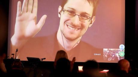 Der NSA-Enthüller Edward Snowden winkt während einer Videoschalte dem Publikum zu. Der US-Whistleblower Edward Snowden ist Vater geworden.
