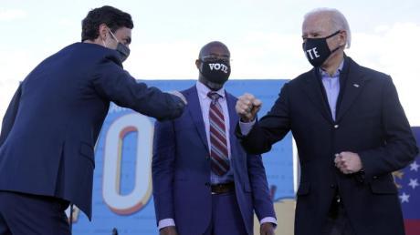 Joe Biden (r) steht während einer Wahlkampfveranstaltung der demokratischen Kandidaten für den US-Senat mit Jon Ossoff (l) und Raphael Warnock auf der Bühne.