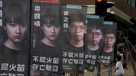 Der prominente Aktivist Joshua Wong (auf den hinteren drei Bannern zu sehen) sitzt wegen des Vorwurfs der illegalen Organisation eines Protests im Gefängnis.