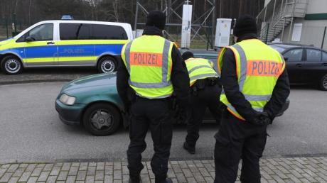 Polizisten kontrollieren ein Fahrzeug vor einem Grenzübergang nach Polen.
