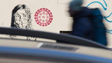 Das neue Virus kommt: Was dieses Streetart-Kunstwerk im Berliner Kiez Prenzlauer Berg zeigt, fürchten Bürger, Politik und Mediziner auch in der Realität.