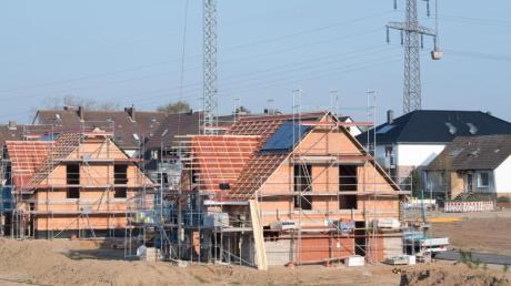 Einfamilienhäuser stehen im Rohbau in einem Neubaugebiet in der Region Hannover.