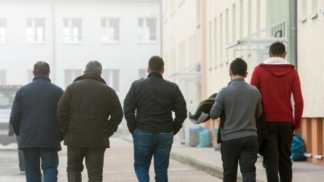 Männliche Asylbewerber gehen über das Gelände der Zentralen Ausländerbehörde (ZABH) in Eisenhüttenstadt.
