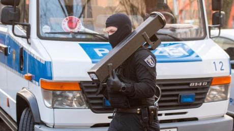 Ein Polizeibeamter trägt nach einer Razzia im Märkischen Viertel in Berlin eine Ramme.