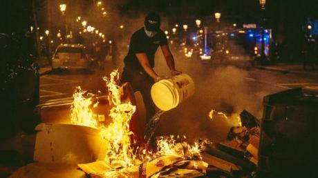 Ein Mann versucht bei den Protesten in Barcelona, ein Feuer zu löschen.