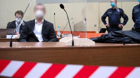 Der wegen versuchten Mordes in 31 Fällen, schwerer Brandstiftung und Vorbereitung einer schweren staatsgefährdenden Gewalttat angeklagte Mann (2.v.l) sitzt vor Prozessbeginn mit seinem Anwalt im Landgericht in München im Verhandlungssaal.