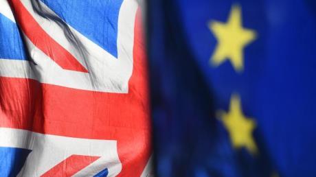 Eine Flagge der Europäischen Union und eine Flagge von Großbritannien wehen vor dem Parlament in Westminster.