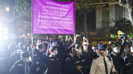 Polizisten hissen vor einem Gericht in Hongkong eine Warnflagge gegen die Unterstützer von 47 pro-demokratischen Aktivisten, die wegen angeblicher Verstöße gegen das neue Sicherheitsgesetz vorerst in Untersuchungshaft bleiben müssen.