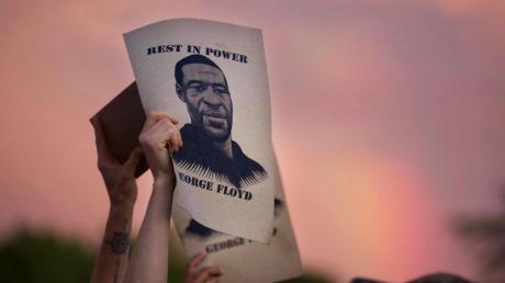 Demonstranten halten während eines Protestes ein Porträt von George Floyd in die Höhe.