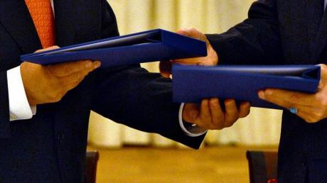 Der damalige Generaldirektor der IAEO, Yukiya Amano (l), und der Leiter der iranischen Atomenergiebehörde, Ali Akhbar Salehi, tauschen am 14.07.2015 in Wien die unterschriebenen Verträge, die das iranische Atomprogramm regeln sollen.