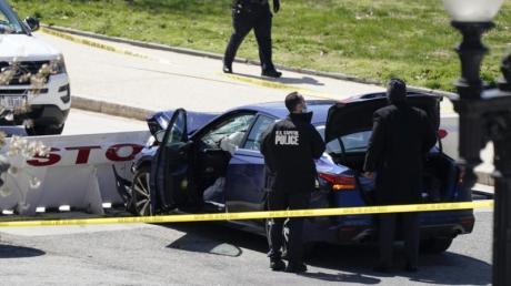 Beamte der Kapitol-Polizei stehen in der Nähe des Autos, das eine Absperrung gerammt hat.