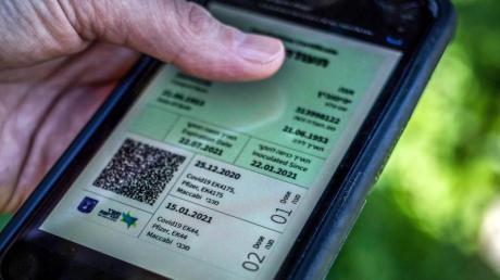 Weg zur Freiheit: Ein israelischer Mann hält ein Smartphone in der Hand, auf dem der sogenannte grüne Pass abgebildet ist.