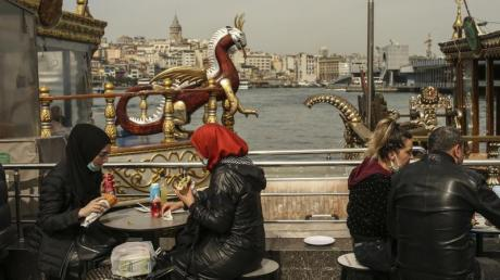 Menschen essen an Tischen am Ufer vom Goldenen Horn auf dem Eminonu Markt in Istanbul.