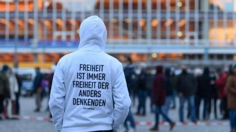 """Ein Teilnehmer einer Kundgebung der """"Querdenker"""" steht im März auf dem Altmarkt in Dresden. (Archivbild)."""