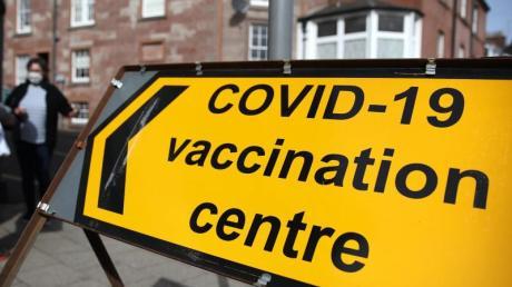 Hinter einem Schild eines Corona-Impfzentrums in Blairgowrie stehen zwei Menschen mit Mund-Nasen-Schutz.