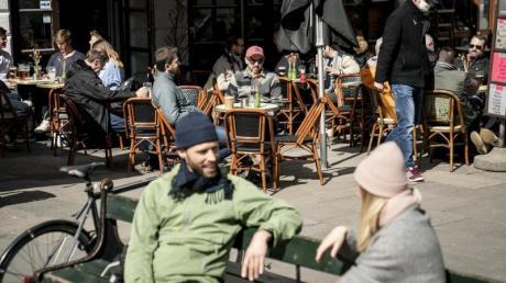Menschen sitzen im belebten Außenbereich eines Cafés in der dänischen Haupstadt Kopenhagen.