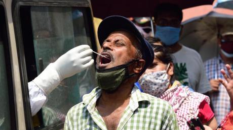 Ein Mitarbeiter des Gesundheitswesens entnimmt in Kalkutta aus einem Auto heraus einen Abstrich für einen Corona-Test.