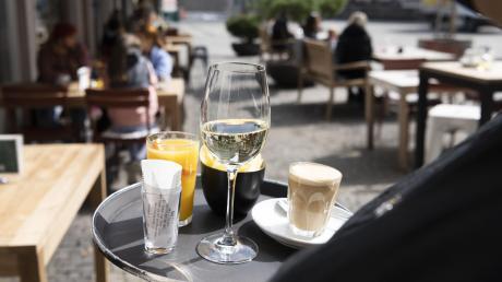 """Das ist kein Archivfoto, sondern neuer Alltag in St. Gallen: Cappuccino, Wein und Orangensaft auf dem Tablett einer Kellnerin der Bar """"Blumenmarkt""""."""
