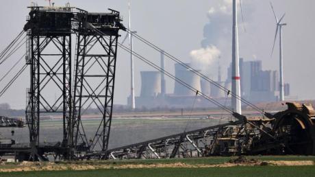 Ein Bagger gräbt am Tagebau Garzweiler, im Hintergrund das Braunkohlekraftwerk Niederaußem - und Windräder. Viel Zeit für ein neues Klimaschutzgesetz bleibt nicht. Die letzte Sitzungswoche des Bundestags vor der Wahl im September ist Ende Juni.