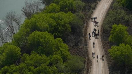 Migranten gehen einen Feldweg in Mission (Texas) entlang, nachdem sie die Grenze zwischen Mexiko und den USA überquert haben.